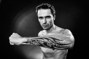 Man showing tatoo on arm hand made in studio - focus on arm, bw