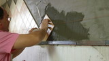 Worker installing Tile to a Kitchen wall