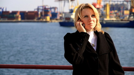 Woman talks on telephone in port