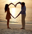 Romantic couple making heart shape with arms on beach at sunset