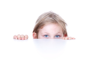 blond little girl hiding behind white table