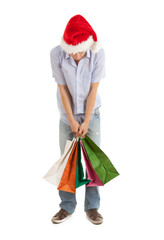 shopping man in christmas hat keeping bags, full length