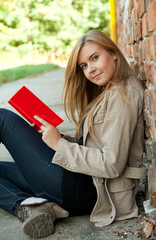 young woman reading book outdoors