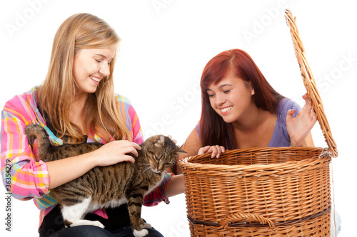 two teenage girls  with cat in wicker basket