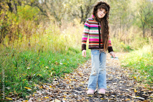 Funky child posing outdoors in colorful blouse