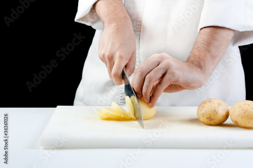 Chef cutting potatoes