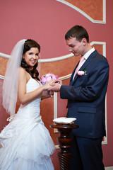 Elegant groom wears a wedding ring a happy bride