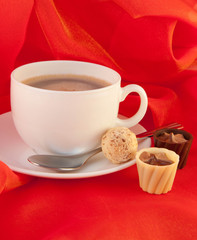 Cup of coffee with chocolates on red silk