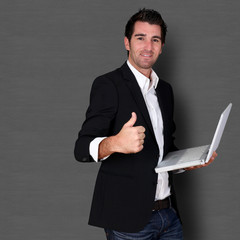 Salesman holding laptop computer and showing thumb up