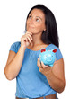 Pensive woman with a blue money-box