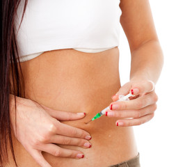 body part of slim girl giving herself insulin shot