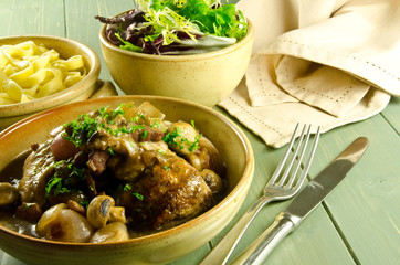 coq au vin with salad and noodles