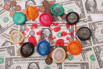 A bloodstained one-dollar bill and colored condoms