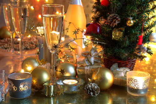 Champagne,baubles,candle lights and christmas tree.