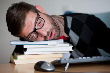 Tired nerd falling asleep on a bunch of books