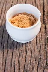 small cup of brown sugar on wood teak