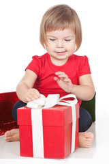 Little girl opening the red gift