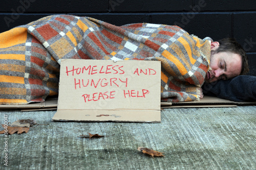 Young homeless man sleeping on sidewalk