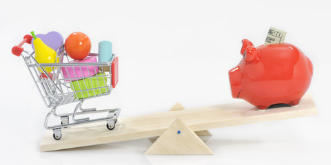 Saving and overspending; savings pig and shopping cart