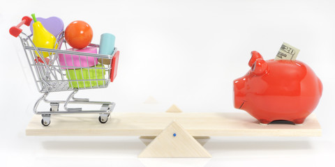 Saving and balanced spending; savings pig and shopping cart