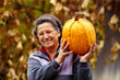 Old woman holding large pumpkin