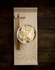 Riso in bianco in ciotola con bastoncini asiatici