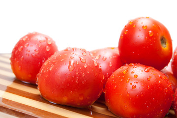 Red ripe tomatoes on a wooden board with water drops