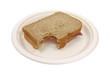Bitten corned beef sandwich on paper plate