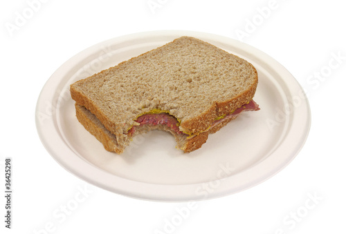 Bitten corned beef sandwich on paper plate