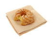 Cruller doughnut on cloth napkin bitten