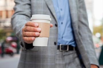 Businessman holding disposable cup