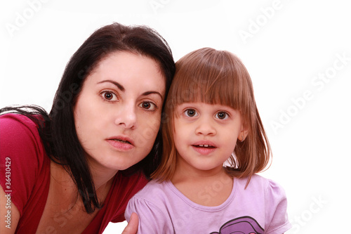 Mother and cute little daughter watch TV in great concentration