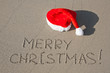 Merry Christmas written on the sand beach under red Santa hat