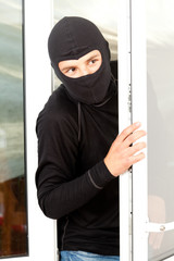 burglar  in mask breaking into house through window