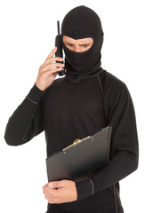 young male thief in balaclava with mobile phone