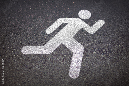 runner sign on asphalt road