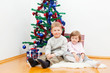 brother and the sister sit near the dressed up New Year tree