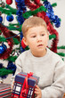 little boy sits with a gift near the dressed up New Year tree
