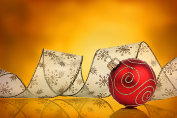 Red christmas bauble with curled ribbon and vivid background