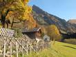 Bergsiedlung im Herbst mit Zaun und Kapelle