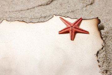 Old paper tag on natural sand with starfish