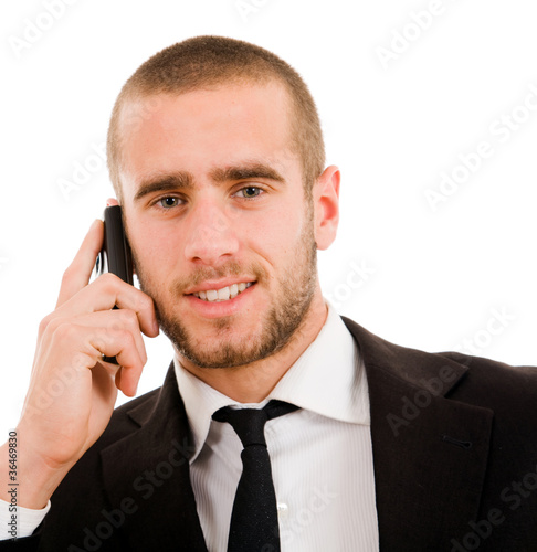Close-up of young business man talking on the mobile phone, over