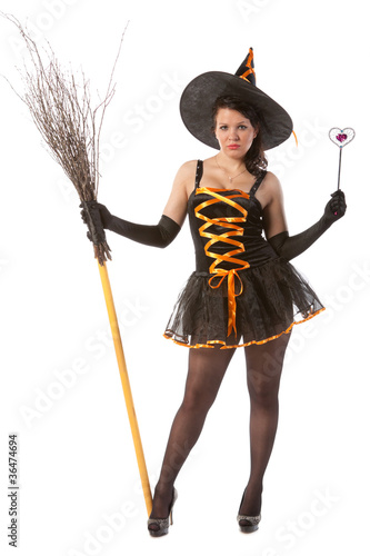 sexy girl in Halloween witch with broom and wand