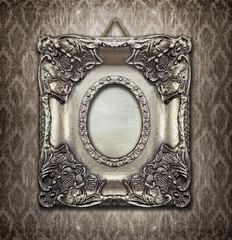 Ornamental silver frame on an aged damask wallpaper