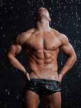 Mięśni mokre sexy młoda nagi mężczyzna stwarzających w deszczu w studio