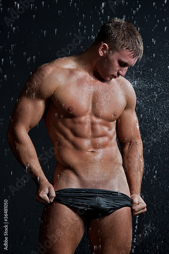 Muscle wet sexy young naked man posing under the rain in studio