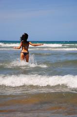 una ragazza corre nel mare