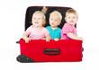 children sitting inside red suitcase