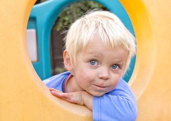 Cute blond boy playing in  climbing frame