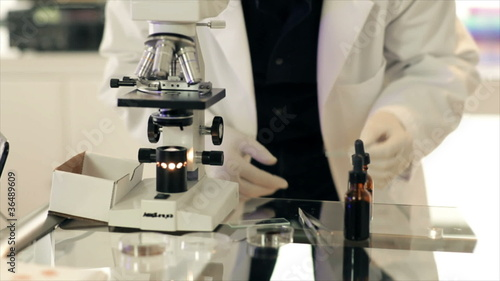 Lab Tech Looks into Microscope